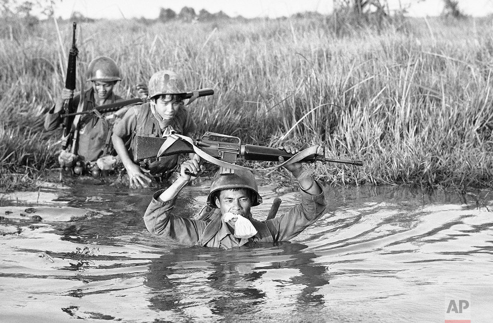 A South Vietnamese soldier holds his personal belongings in a plastic bag between his teeth as his unit crosses a muddy Mekong Delta stream in Vietnam near the Cambodian border on March 11, 1972. His unit is not part of a new large operation into Cambodia but charged with stemming Communist infiltration from Cambodia into South Vietnam in the heavily populated Mekong Delta area. (AP Photo/Nick Ut)