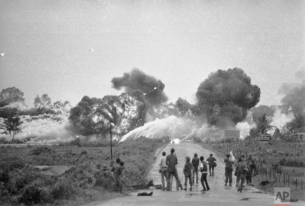 Napalm bombs explode and spread fire during fighting in Trang Bang, Vietnam, June 8, 1972.  Strike by a Skyraider plane was misplaced and injured civilians fleeing the area, occupied in recent days by North Vietnamese forces.   (AP Photo/Nick Ut)