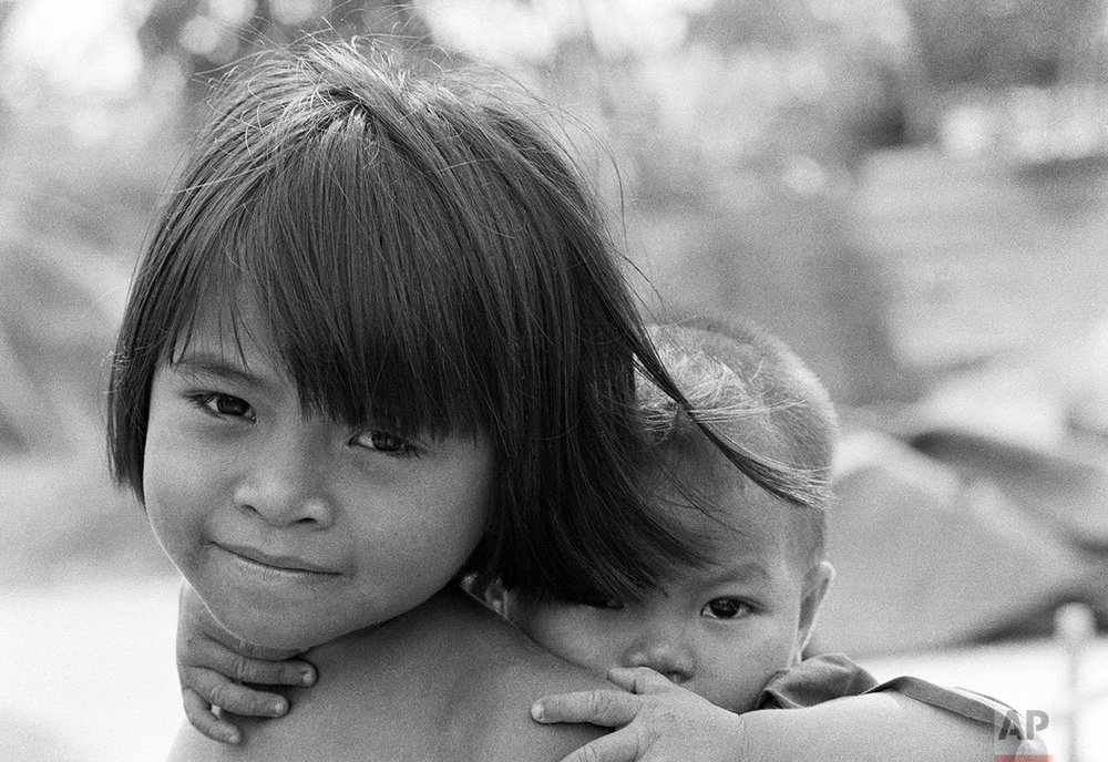 A young South Vietnamese girl and her little brother pose for a portrait northeast of Saigon, Jan. 2, 1974. (AP Photo/Nick Ut)
