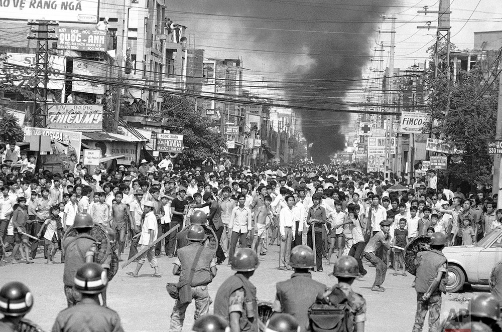 As smoke billows from a burning motorcycle, South Vietnamese riot police face several thousand angry protesters who sought to move their anti-corruption demonstration from suburban Saigon to the center of the city on Oct. 31, 1974. Authorities contained the crowd. (AP Photo//Nick UT)