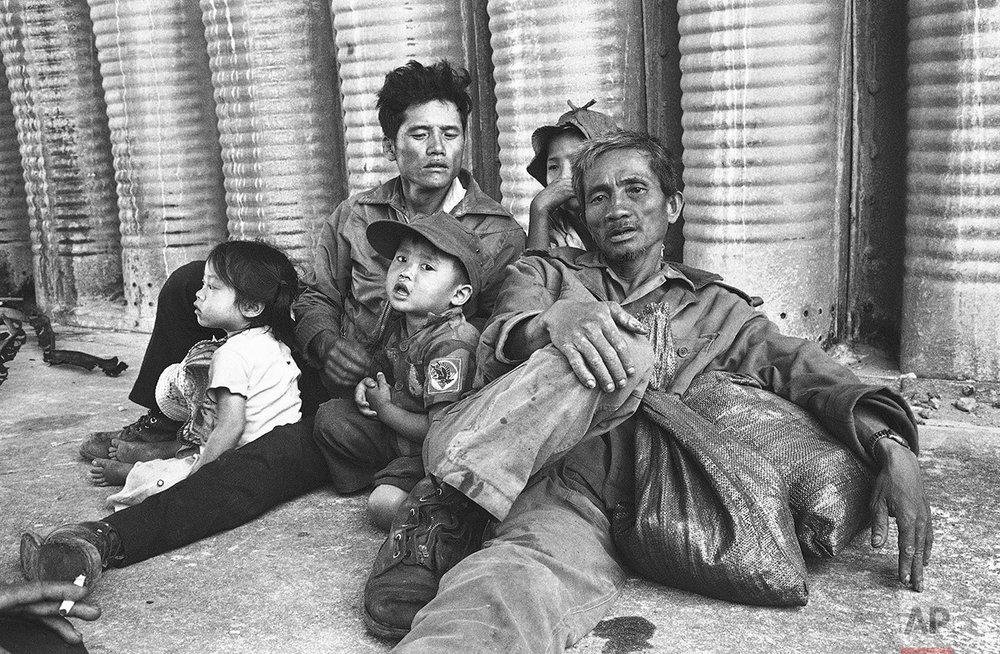 Weary and hungry, a refugee family rests at Tuy Hoa Airfield in Vietnam on March 27, 1975 following their arrival. They were among the thousands of civilians and military who fled the central Highlands provinces. (AP Photo/Nick Ut)