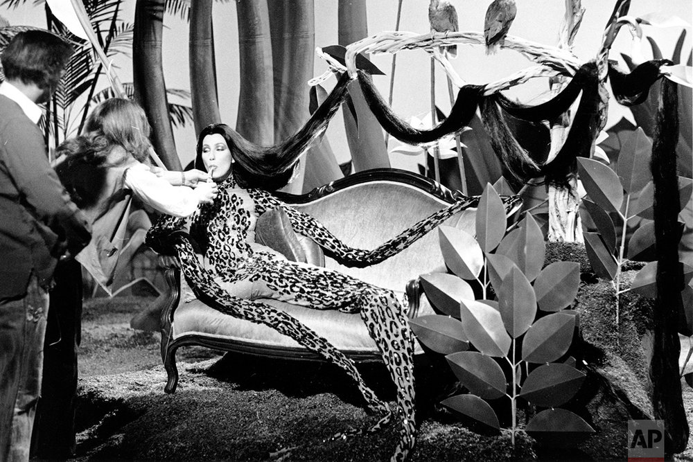 "Entertainer Cher is fed a drink of water through a straw by a stagehand during a pause in the taping of NBC-TV's ""Cher...And Other Fantasies"" in Los Angeles, Ca., Friday, Feb. 16, 1979.  Cher is portraying a stylized leopard in a jungle scene.  (AP Photo/Nick Ut)"