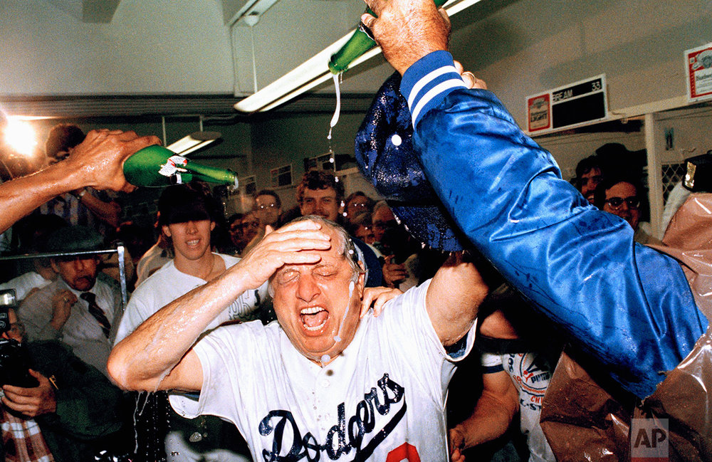 Los Angeles Dodgers Manager Tom Lasorda wipes the champagne from his face in the locker room on Friday, Oct. 1, 1983 after the Dodgers clinched the National League West title in Los Angeles, beating the San Francisco Game 4-3. (AP Photo/Nick Ut)