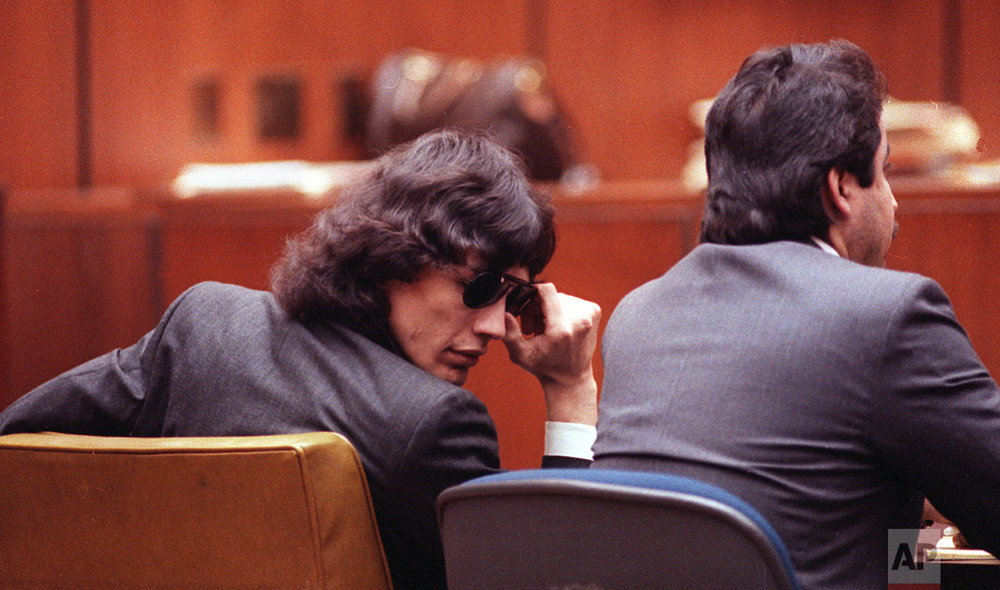 Richard Ramirez adjusts his sunglasses in the courtroom during a special hearing in Los Angeles, Ca., Monday, Feb. 27, 1989.  Ramirez, known as the Night Stalker, is on trial for thirteen counts of murder committed in 1985.  At right is his attorney, Daniel Hernandez.  Ramirez was born Feb. 28, 1960.  (AP Photo/Nick Ut)