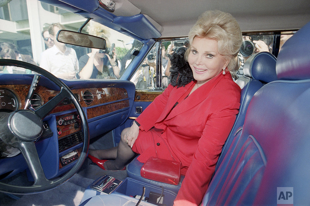"Zsa Zsa Gabor sits in her Rolls-Royce Corniche convertible as she leaves court at lunch break of her cop-slapping trial on Sep. 28, 1989 in Beverly Hills, Calif. Gabor threatened to call police on a mob of reporters who surrounded the car as she awaited a jury verdict. ""Don't scratch the car,"" she snapped at the media mob. (AP Photo/Nick Ut)"