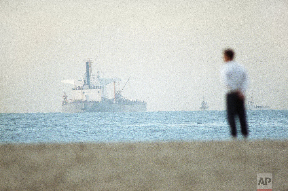 The 811-foot tanker American Trader sits offshore of Huntington Beach, California Thursday, Feb. 8, 1990 after spilling 295,000-plus gallons of oil. Offshore winds condensed the major spill into a roundish mile-long blob, helping crew in their cleanup efforts, authorities said. (AP Photo/Nick Ut)