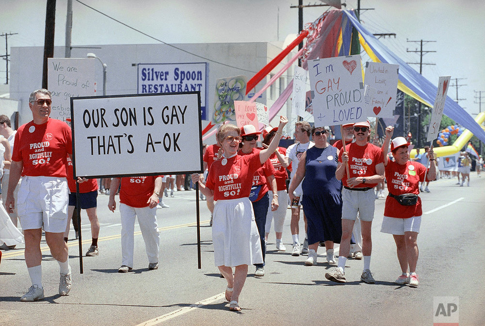 "Gay men and women and their parents march together in a show of unity during the Los Angeles Gay and Lesbian Pride Parade, Sunday, June 23, 1990, West Hollywood, Calif. Thousands lined the streets to see celebrities, marching bands, and floats illustrating the parade's theme, ""Look to the Future."" (AP Photo/Nick Ut)"