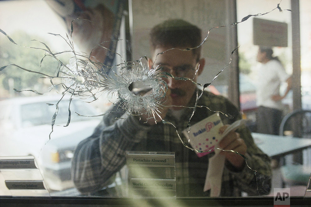 Customer Greg Furie eats Ice cream at a Baskins-Robbins store, Monday, March 3, 1997 in the North Hollywood section of Los Angeles near the site of last Friday's bank shootout. Most of the bullet-damaged business in the area were open on Monday, including the bank. (AP Photo/Nick Ut)