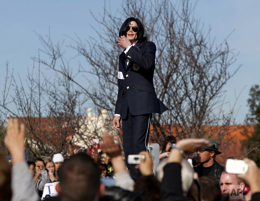 Michael Jackson waves to his fans from atop his limousine after his arraignment on child molestation charges Friday morning, Jan. 16, 2004, at the courthouse in Santa Maria, Calif.  (AP Photo/Nick Ut)