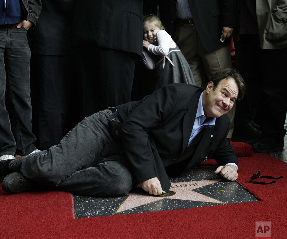 Actor Dan Aykroyd lies down on the newly-dedicated star at the posthumous ceremony Thursday, April 1, 2004 , of the 2,250th star on the Hollywood Walk of Fame for comedian John Belushi in Los Angles. (AP Photo/Nick Ut)