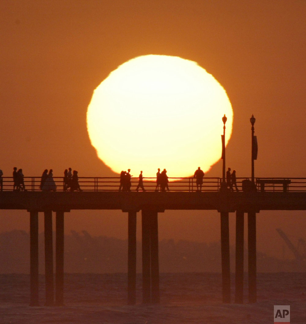 People gather on a pier in Huntington Beach California as the sun sets over Huntington  Beach Saturday, May 29, 2004. (AP Photo/Nick Ut)