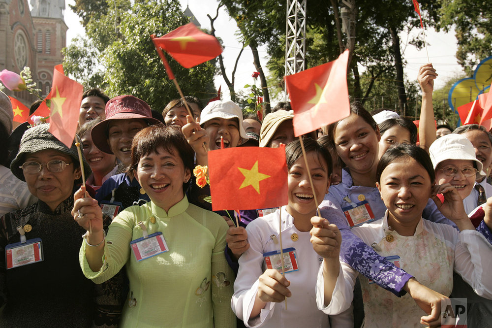 Vietnamese wave flags during an anniversary celebration in Ho Chi Minh City Vietnam Saturday, April 30, 2005. Vietnam celebrated the communist victory over a U.S.-backed government Saturday, parading troops on the same boulevard used by tanks on their way to smashing the Presidential Palace of South Vietnam 30 years ago. (AP Photo/Nick Ut)