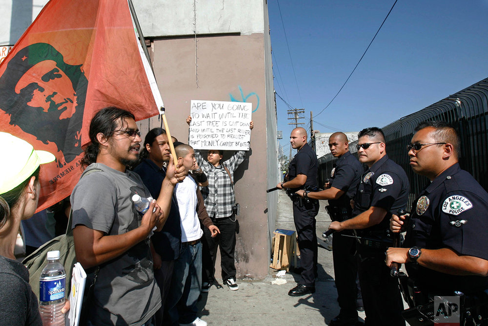 A group of demonstrators stands in front of a line of Los Angeles Police officers during a protest outside of the 14-acre South Central urban community garden in South Los Angeles, Tuesday, June 13, 2006. Sheriff's deputies and police evicted farmers and supporters from the community garden being reclaimed by the landowner, making arrests as protesters resisted by occupying a tree, chaining themselves to barrels of concrete and blocking traffic with demonstrations in nearby streets. (AP Photo/Nick Ut)