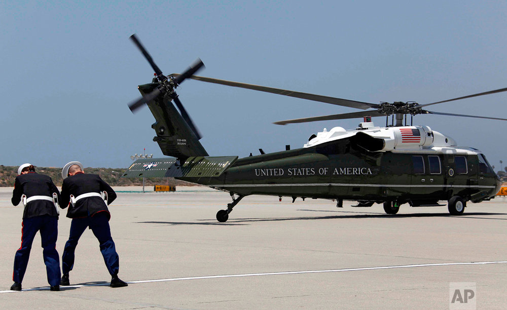 Two U.S. Marines shield themselves from the prop wash from Marine One, carrying President Barack Obama as it lifts off at Los Angeles International Airport Wednesday May 27, 2009.   (AP Photo/Nick Ut)