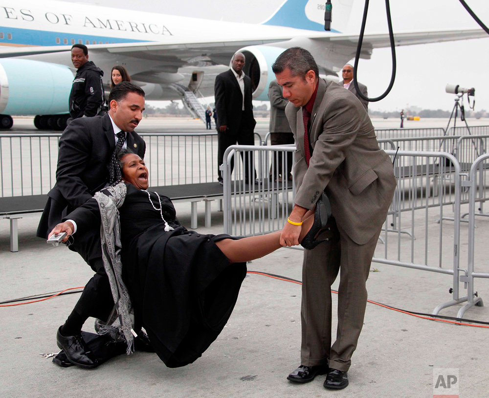 Los Angeles International Airport police remove Brenda Lee from near Air Force One after Lee attempted to give President Obama a letter, Thursday, May 28, 2009, at Los Angeles International Airport in Los Angeles. Lee never got close to President Obama and she was released after being questioned. (AP Photo/Nick Ut)