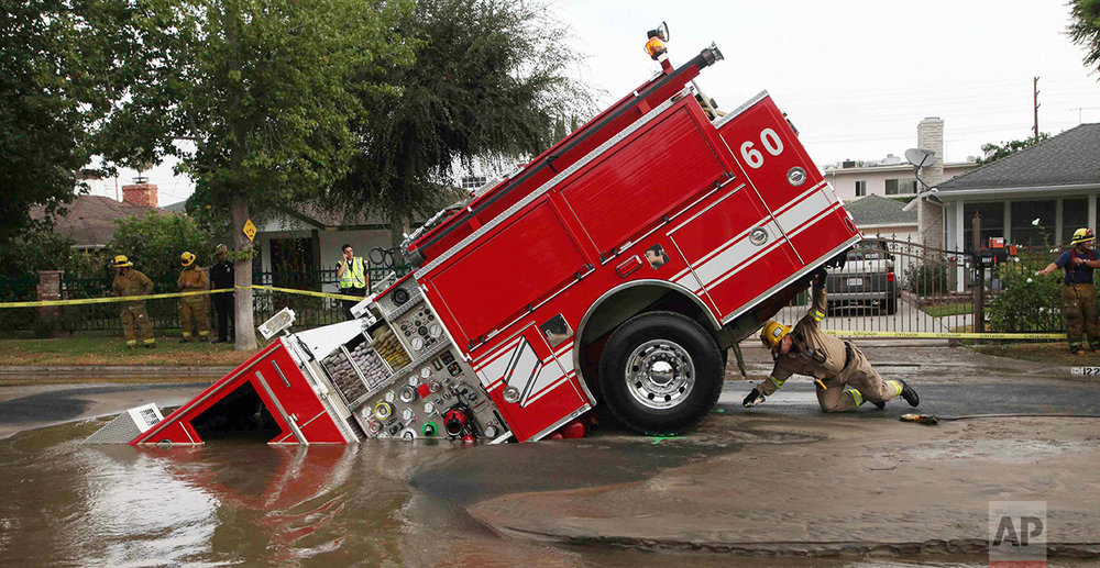 A Los Angeles fireman looks under a fire truck stuck in a sinkhole in the Valley Village neighborhood of Los Angeles Tuesday, Sept. 8, 2009. Four firefighters escaped injury early Tuesday after their fire engine sunk into a large hole caused by a burst water main in the San Fernando Valley, authorities said.  (AP Photo/Nick Ut)