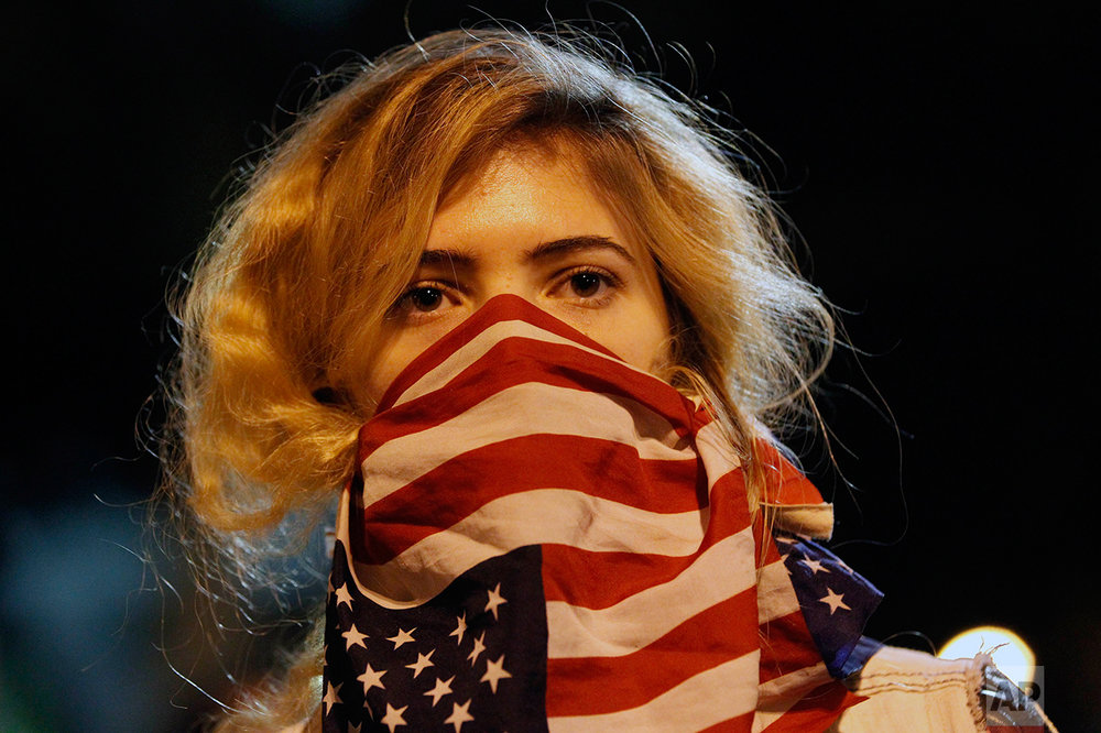 A woman wears a U.S. flag in front of her face during a rally near the Los Angeles Police Department headquarters in downtown Los Angeles on Tuesday, Nov. 25, 2014. People protesting the Ferguson Mo., grand jury decision took to the streets in cities across the U.S. for the second day. (AP Photo/Nick Ut)