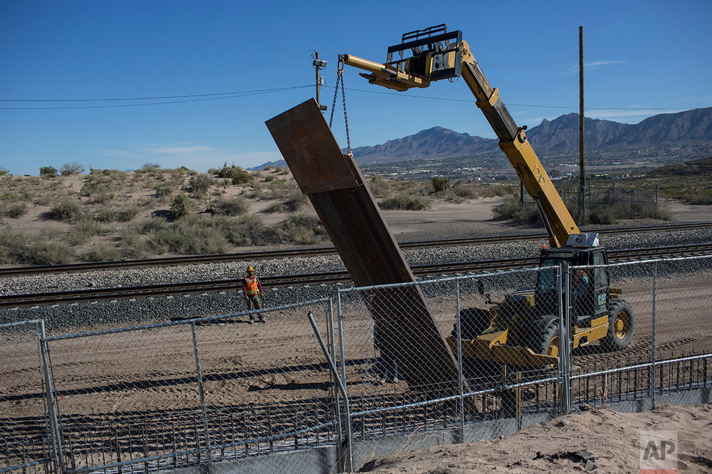 Workers use a crane to lift a segment of a steel border fence on the U.S. side of the border with Mexico, where Sunland Park, New Mexico meets Ciudad Juarez, Mexico, Thursday, March 30, 2017. Residents on the Mexico side estimate 15 to 20 panels go up daily. (AP Photo/Rodrigo Abd)