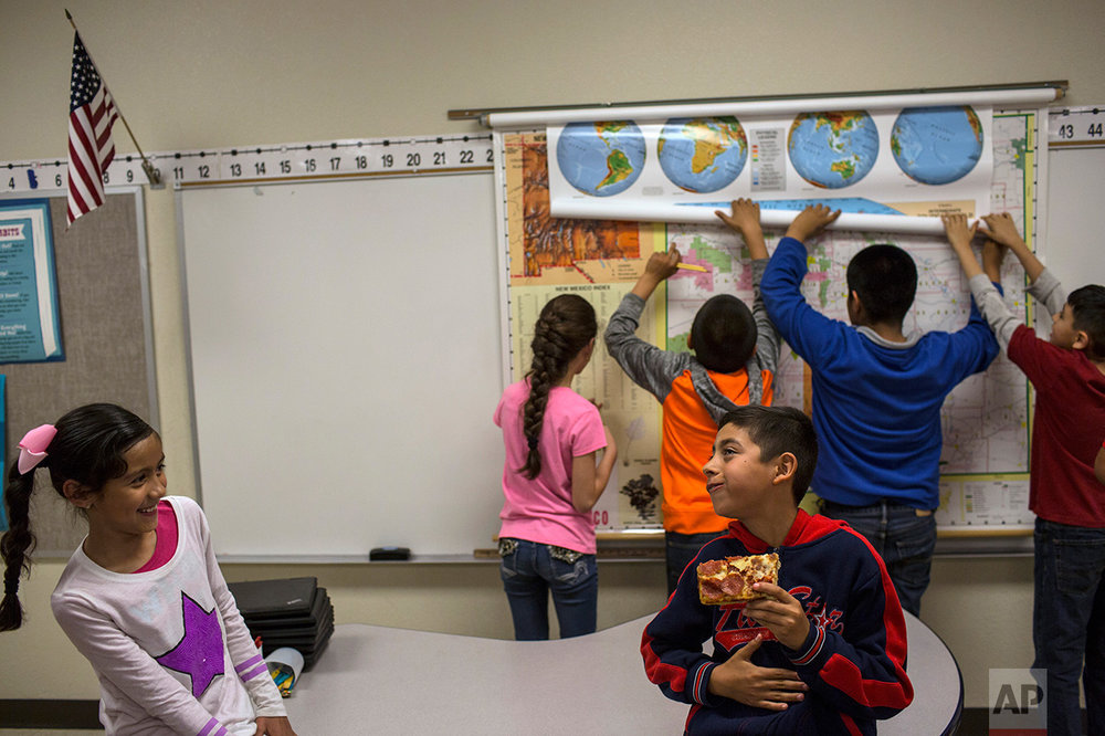 A student eats a slice of pizza during a break in a fourth grade classroom at Columbus Elementary School, in Columbus, New Mexico, Friday, March 31, 2017. (AP Photo/Rodrigo Abd)