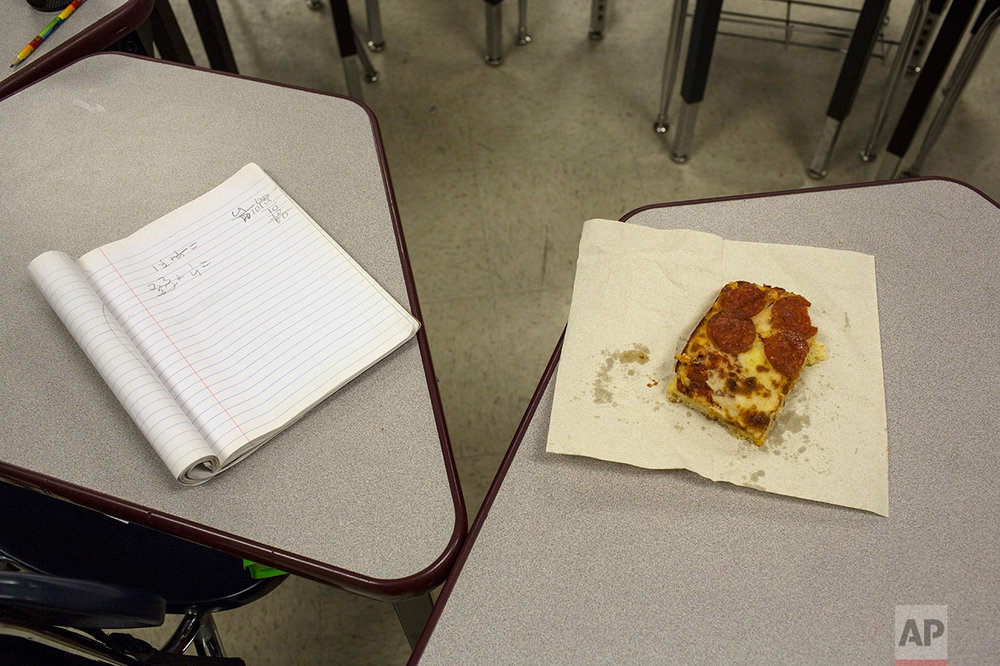 A student's slice of pizza beside a notebook in a classroom at Columbus Elementary School, in Columbus, New Mexico, US, Friday, March 31, 2017. (AP Photo/Rodrigo Abd)