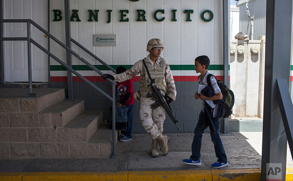 Students from Columbus Elementary School, walk next to a Mexican soldier while crossing  the border from Columbus, New Mexico, US, into Palomas, Mexico, after school, Friday, March 31, 2017. (AP Photo/Rodrigo Abd)