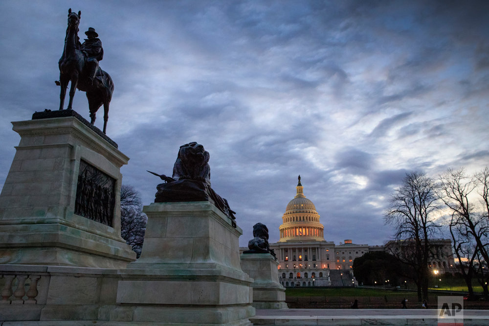 A statue of Civil War General Ulysses S. Grant, left, stands near the U.S. Capitol at dawn in Washington, Thursday, March 30, 2017. (AP Photo/J. Scott Applewhite)
