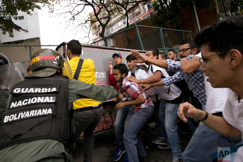 Venezuelan Bolivarian National guard officers are confronted by university students during a protest outside of the Supreme Court in Caracas, Venezuela, Friday, March 31, 2017. Venezuelans have been thrust into a new round of political turbulence after the government-stacked Supreme Court gutted congress of its last vestiges of power, drawing widespread condemnation from foreign governments and sparking protests in the capital. (AP Photo/Ariana Cubillos)
