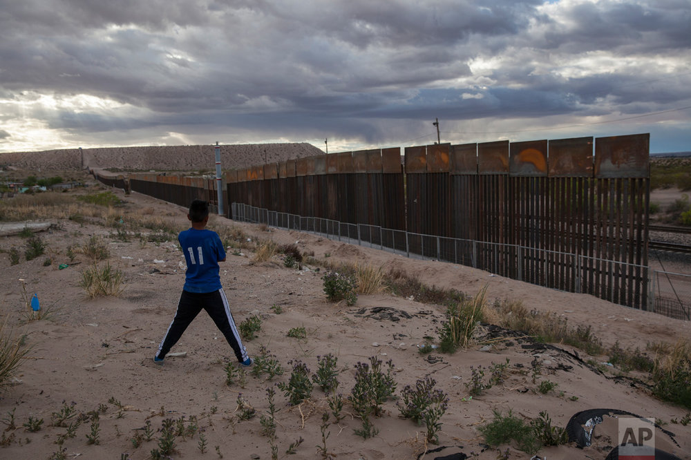 A boy looks at a new, taller fence being built along U.S.-Mexico border, replacing the shorter, gray fence in front of it, in the Anapra neighborhood of Ciudad Juarez, Mexico, Wednesday, March 29, 2017, across the border from Sunland Park, N.M. (AP Photo/Rodrigo Abd)