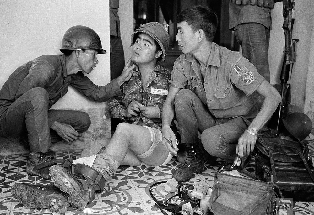 A wounded Nick Ut, attended by two South Vietnamese soldiers in July 1972 at Trang Bang, the same village where a month earlier Ut made his famous photo of Kim Phuc burned by napalm. (AP Photo/Neal Ulevich)