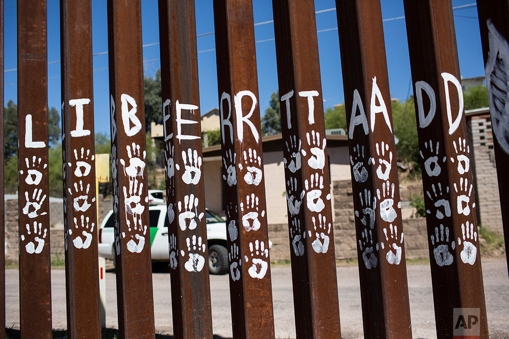 "Handprints and the Spanish word for ""Liberty"" mark slats of the US-Mexico border fence in Nogales, Mexico, Sunday, April 2, 2017. (AP Photo/Rodrigo Abd)"