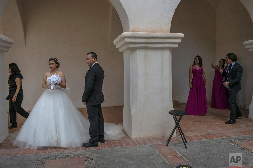 Newlyweds Aldo and Brenda Norris wait for their wedding photographer outside a church in Caborca, Sonora state, Mexico, Saturday, April 1, 2017. Caborca lies in traditional tribal lands of the Tohono O'odham indigenous people, a region that straddles the U.S.-Mexico border in the states of Arizona and Sonora. (AP Photo/Rodrigo Abd)