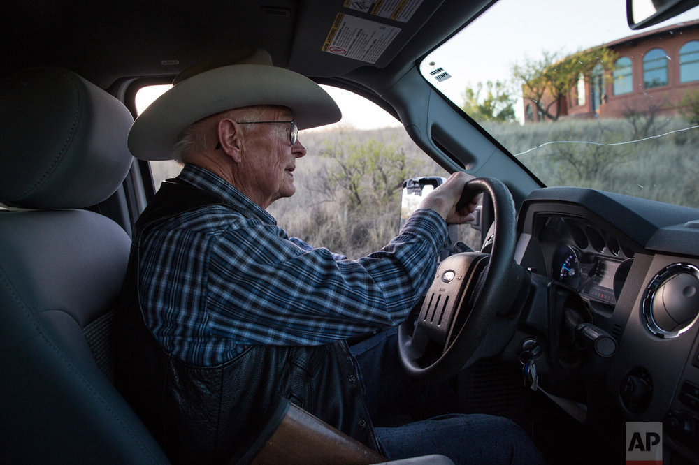 Rancher Jim Chilton drives his pick-up truck on his property which includes a 5 ½-mile stretch of border that's marked only by a four-strand barbed wire fence, in Arivaca, Ariz., Sunday, April 2, 2017. (AP Photo/Rodrigo Abd)