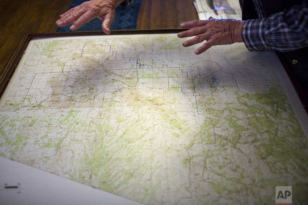 Rancher Jim Chilton shows uses a map to show the threats he says he faces from drug traffickers on his 50,000-acre ranch along the US-Mexico border in Arivaca, Ariz., Sunday, April 2, 2017. (AP Photo/Rodrigo Abd)