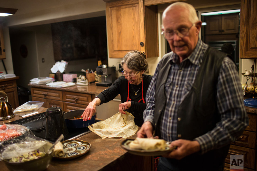 Rancher Jim Chilton prepares dinner with his wife Sue, inside the home of their 50,000 acre ranch in Arivaca, Arizona, Sunday, April 2, 2017. (AP Photo/Rodrigo Abd)