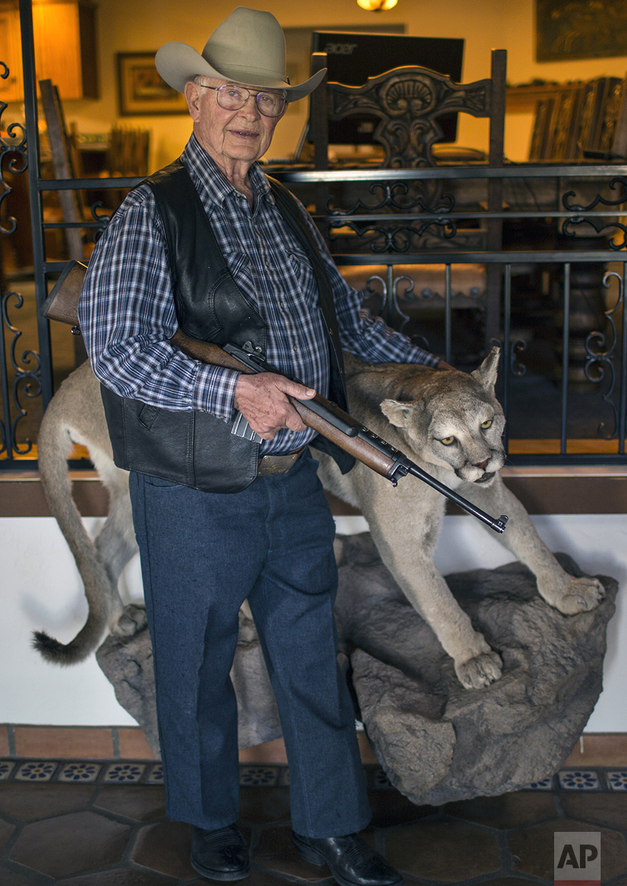 Rancher Jim Chilton poses for a photo next to a taxidermied mountain lion at his ranch in Arivaca, Ariz., Sunday, April 2, 2017. (AP Photo/Rodrigo Abd)