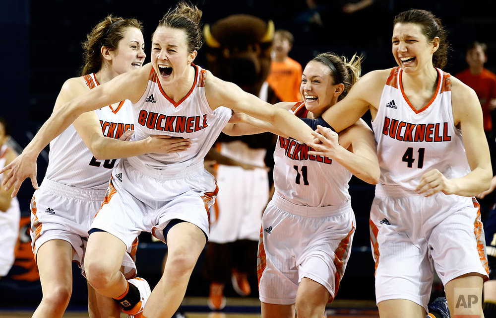 Bucknell's Kate Walker (20), Claire DeBoer (12), Megan McGurk (11) and Sune Stewart (41) celebrate after defeating Navy in overtime of an NCAA college basketball Patriot League Championship game in Lewisburg, Pa., Sunday, March 12, 2017. (AP Photo/Chris Knight)