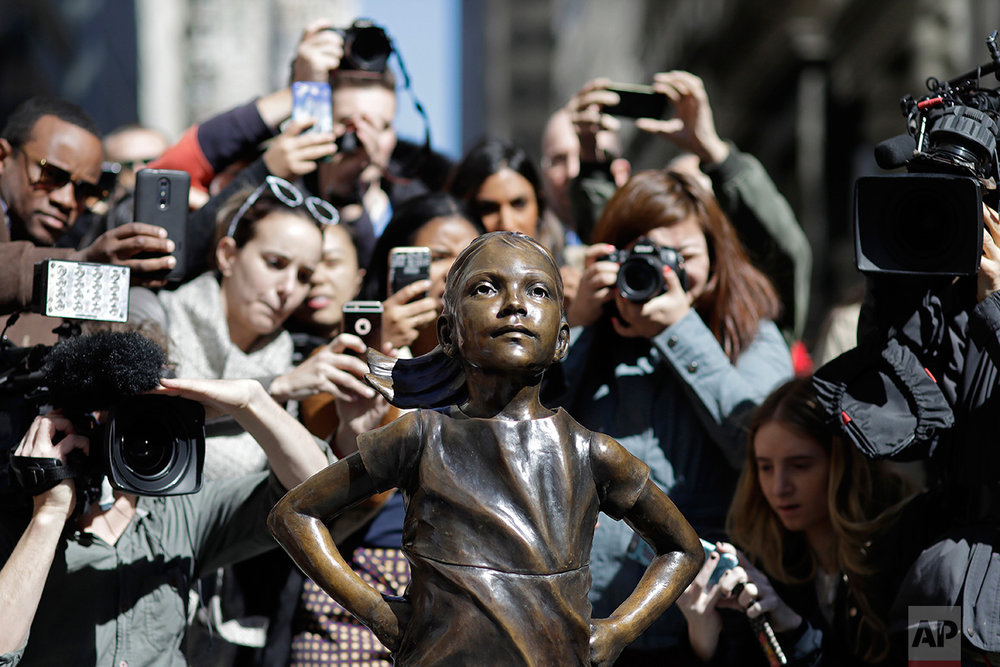 """People stop to photograph the """"Fearless Girl"""" statue, Wednesday, March 8, 2017, in New York. The statue was installed by investment firm State Street Global Advisors. An inscription at the base reads, """"Know the power of women in leadership. She makes a difference."""" (AP Photo/Mark Lennihan)"""