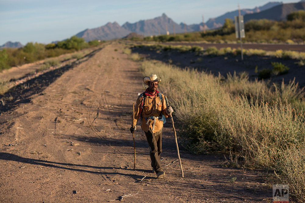 Mark Hainds, a 48-year-old junior community college forestry professor from Andalusia, Alabama, walks on the shoulder of a road near Why, Ariz., Monday, April 3, 2017. (AP Photo/Rodrigo Abd)