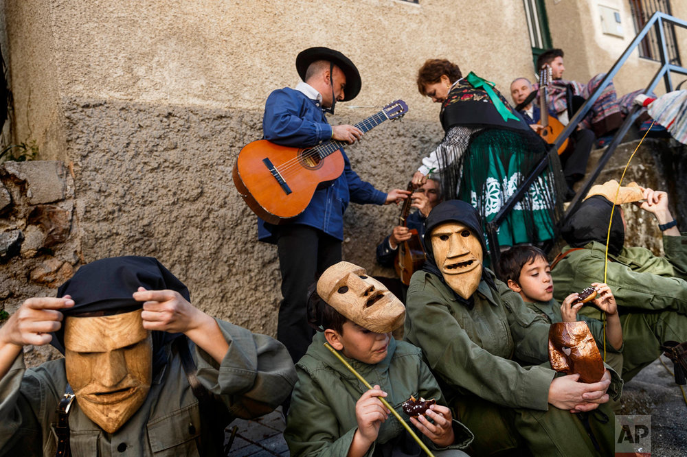 In this April 1, 2017 picture, revelers from San Pedro Bernardo village wearing the traditional 'Machurrero' mask and outfit rest and eat after a parade during a gathering of different villages' carnival masks and characters in the small village of Casavieja, Spain, Monday, April 3, 2017. These festivals, held across central and northwestern Spain, most often coincide with festivities celebrating the advent of spring, mixing Carnival and bizarre pagan-like rituals with mock battles between good and evil.(AP Photo/Daniel Ochoa de Olza)