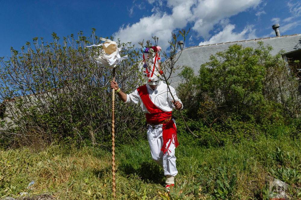 In this April 1, 2017 picture, a reveler in a mask from the traditional La Vijanera de Silio carnival runs after picking a branch from a tree during a parade at a gathering of different villages' carnival masks and characters in the small village of Casavieja, Spain, Monday, April 3, 2017. (AP Photo/Daniel Ochoa de Olza)
