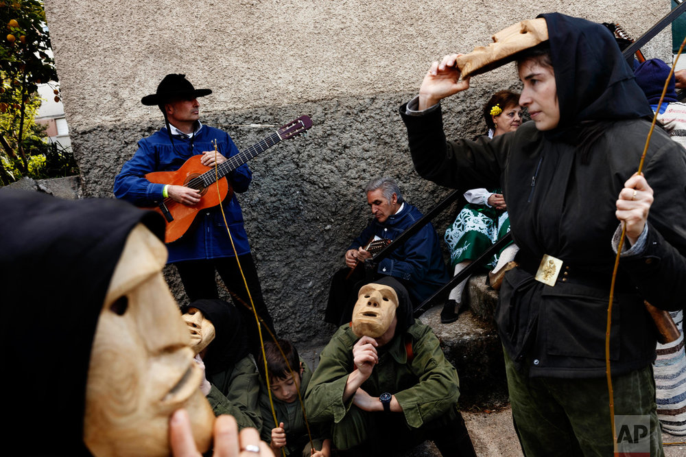 In this April 1, 2017 picture revelers from San Pedro Bernardo village wearing the traditional 'Machurrero' mask and outfit rest after a parade during a gathering of different villages' carnival masks and characters in the small village of Casavieja, Spain, Monday, April 3, 2017. (AP Photo/Daniel Ochoa de Olza)