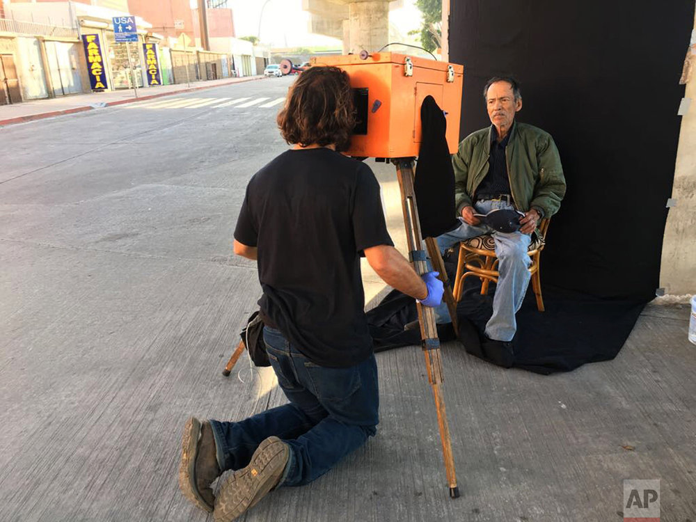 AP photographer Rodrigo Abd uses a wooden box camera to make a portrait of Mexican retiree Miguel Trejo, in Tijuana, Mexico, Wednesday, April 5, 2017. (AP Photo/Jordi Lebrija)