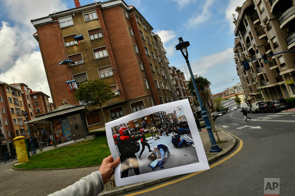 In this photo taken on Tuesday, April 4, 2017, a man holds up an old photo to compare the place where Basque riot police clashed with pro-independence followers during a funeral of one member of the Basque armed separatist group ETA in March 4, 2006, in the Basque village of Santurtzi, northern Spain. (AP Photo/Alvaro Barrientos)