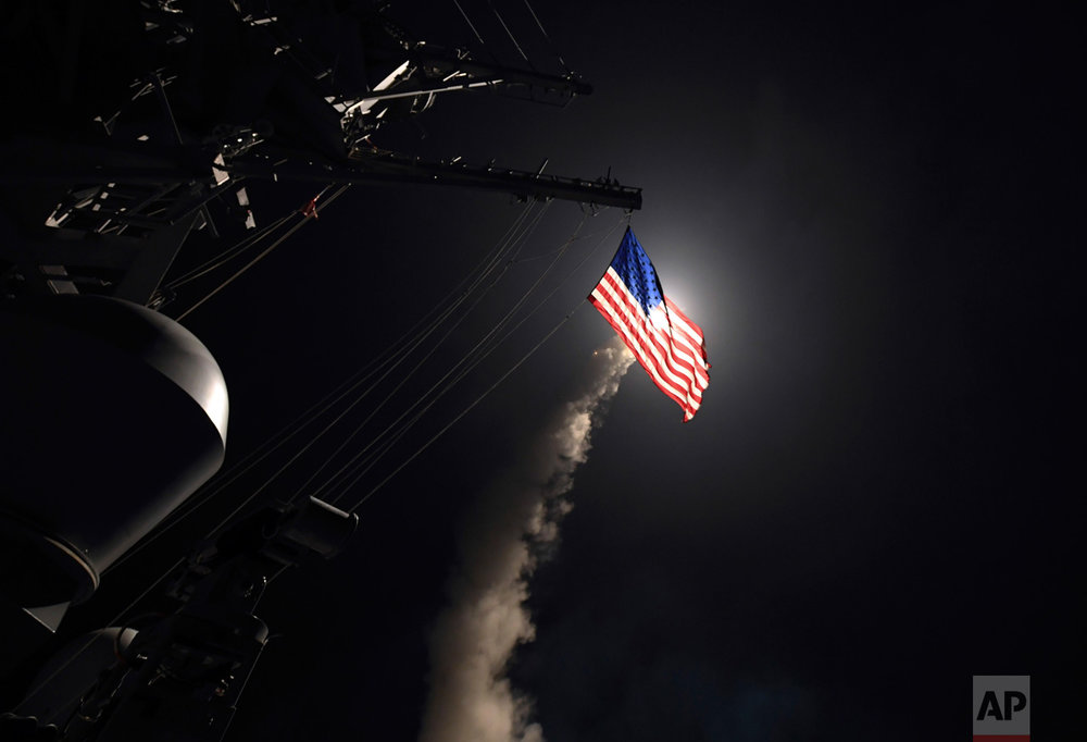 In this image provided by the U.S. Navy, the guided-missile destroyer USS Porter (DDG 78) launches a tomahawk land attack missile in the Mediterranean Sea, Friday, April 7, 2017. The United States blasted a Syrian air base with a barrage of cruise missiles in retaliation for a chemical weapons attack against civilians. (Mass Communication Specialist 3rd Class Ford Williams/U.S. Navy via AP)