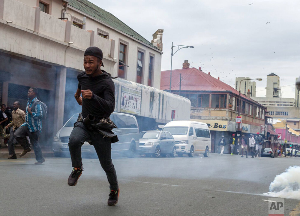Members of the ANC Youth League flee from teargas and rubber bullets fired by police, at the end of a march by the main opposition Democratic Alliance party in Johannesburg, Friday, April 7, 2017. Thousands of South Africans demonstrated in major cities against President Jacob Zuma. Zuma's dismissal of the finance minister has fueled concerns over government corruption and a struggling economy. (AP Photo/Yeshiel Panchia)