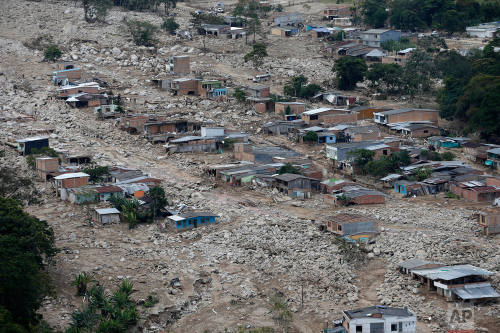 Boulders and debris surround homes on Tuesday, April 4, 2017, after rivers surrounding Mocoa, Colombia overflowed and sent a wall of water and debris surging through the city over the weekend. Authorities said hundreds were killed. (AP Photo/Fernando Vergara)