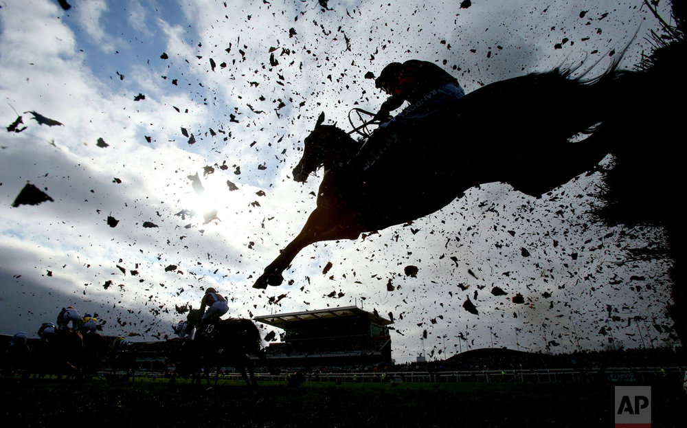 Debris flies as runners and riders clear a fence during the first day of the Grand National Festival at Aintree Racecourse, England, on Thursday April 6, 2017. (Niall Carson/PA via AP)