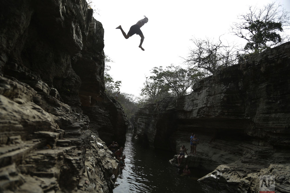 A man jumps into Los Cajones river in Chame, Panama, on Thursday, April 6, 2017. (AP Photo/Arnulfo Franco)