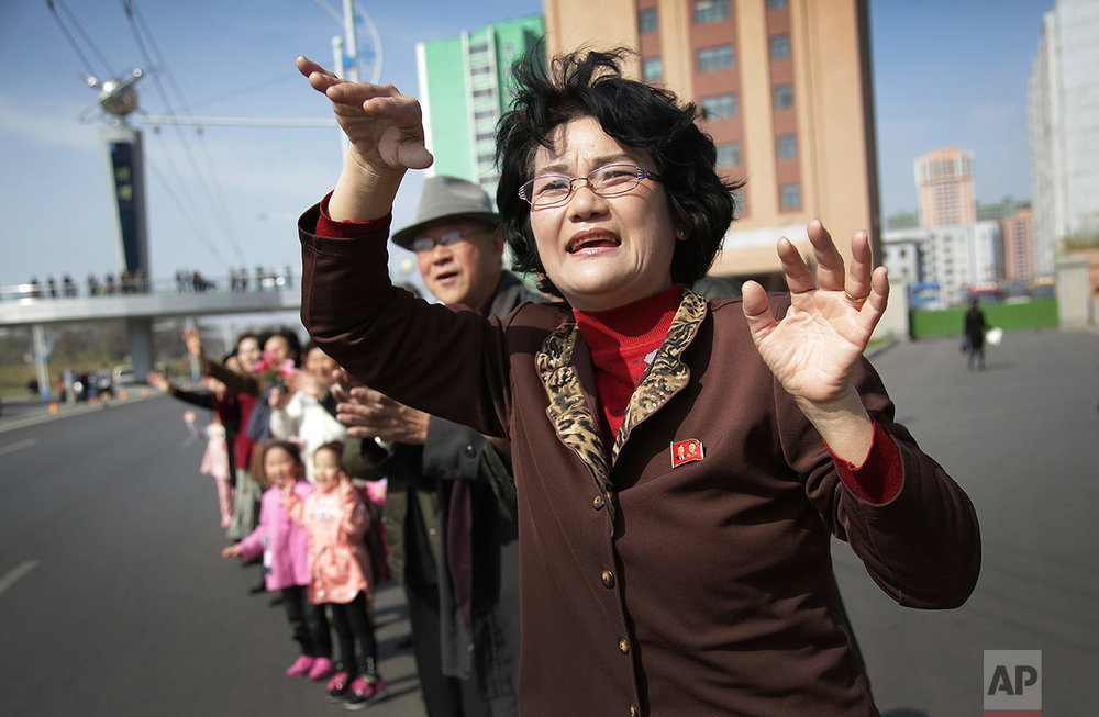 Sin Ye Suk, 50, a resident of Mirae Scientist Street stands in front of her apartment with fellow residents as they cheer on participants of the Pyongyang marathon on Sunday, April 9, 2017, in Pyongyang, North Korea. (AP Photo/Wong Maye-E)