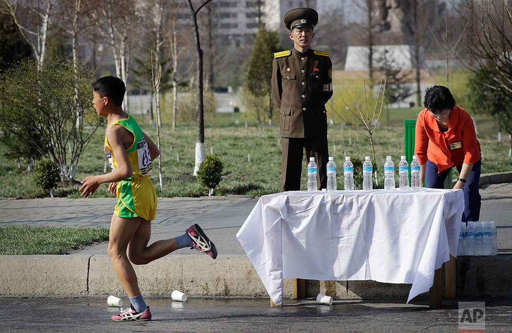 A North Korean military soldier stands on duty while a participant of the Pyongyang marathon runs past a water station on Sunday, April 9, 2017, in Pyongyang, North Korea. (AP Photo/Wong Maye-E)